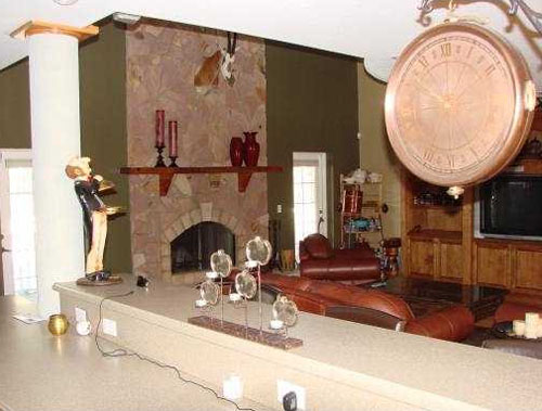 Here's another one where the living room should be the main focus of the photo--not the clock, the candles, the statue, the wires, and the counter.  Taking this on the other side of the counter would have been a much better idea.  This is a $1,399,000 listing in Florida.